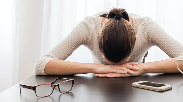Exhausted woman with phone on desk - featured image