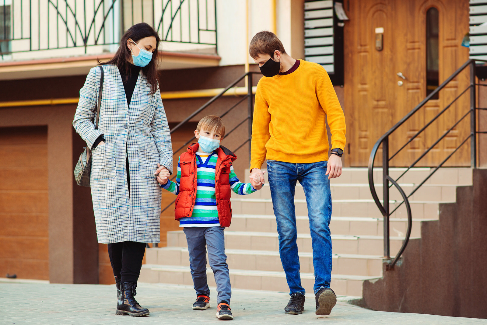 Family goes for a walk while wearing masks