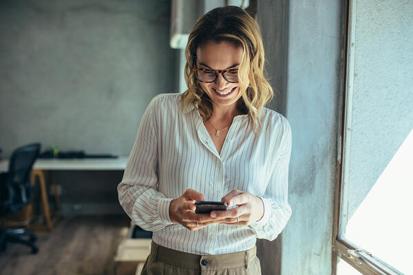 Smiling woman reading update on her phone from the office