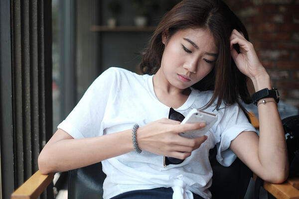 Young Asian woman looking bored scrolling through phone