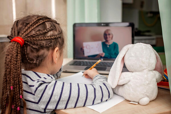 Young girl stays organized by taking notes during virtual lesson